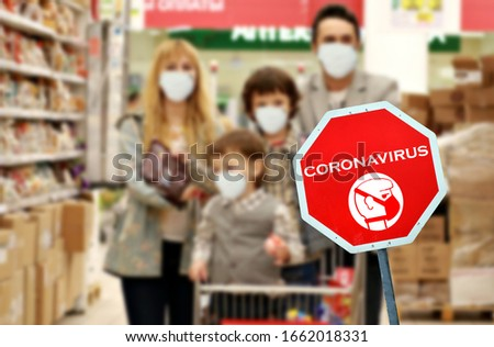 Orange sign warning of pandemic due to Covid-19 or corona virus in supermarket with in purposely blurred background caucasian family wearing protective hygienic masks
