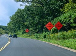 Orange signs warning of UNEVEN LANES, LOW SHOULDER and BUMP along a curvy asphalt highway with cars on road and trees and wild flowers on the side.