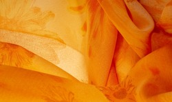 Orange silk fabric with painted meadow flowers, floral background. Many pale flowers in a colorful composition. Background texture