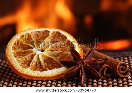 orange slice with anis and cinamon sticks on bamboo mat in front of fireplace