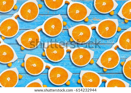 Orange sliced sunglasses on a blue rustic wood background, Summer fruit and fashion concept #614232944