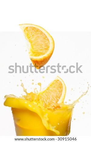 Orange slices fall in juice - stock photo