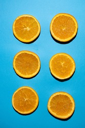 Orange slices parallel to each other in a vertical photo on a blue background