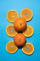 Orange slices parallel to each other with two whole oranges centered in a vertical photo on a blue background.