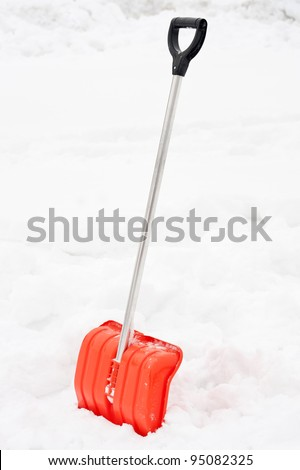 Orange snow shovel stick in snowdrift.