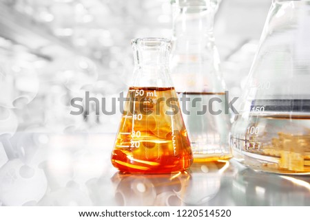 orange so in conical three flasks with chemical structure in science education laboratory background