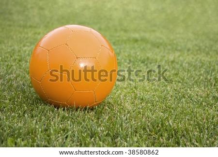 Orange soccer ball on the grass