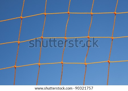 Orange soccer goal net against blue sky