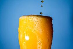 Orange soda large glass, overflowing glass of orange soda closeup with bubbles on blue background