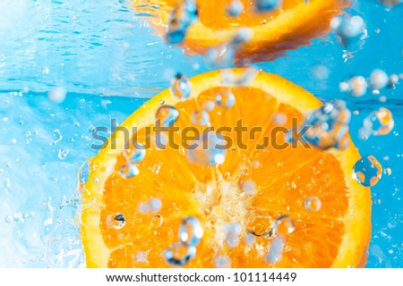 Orange splash in water, top view, bubbles with fruit reflection