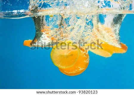 Orange splashing in water with blue background