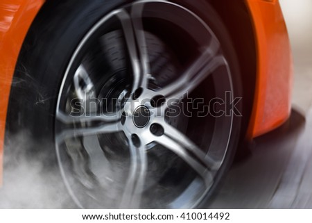 Orange Sport Car with detail on spinning and smoking wheels/tires doing burnouts, dynamic photo