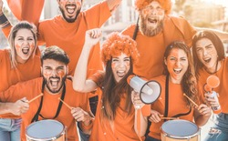 Orange sport fans screaming while supporting their team out of the stadium - Football supporters having fun at competion event - Champions and winning concept - Focus on center girl face
