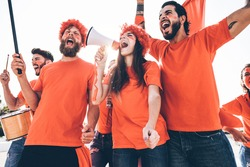 Orange sport fans screaming while supporting their team out of the stadium - Football supporters having fun at competion event - Soft focus on center girl face