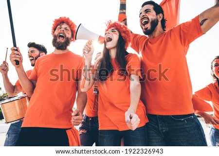 Orange sport fans screaming while supporting their team out of the stadium - Football supporters having fun at competion event - Soft focus on center girl face Foto stock ©