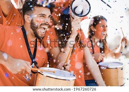 Orange sport fans screaming while supporting their team out of the stadium - Football supporters having fun at competion event - Focus on man face Stock foto ©