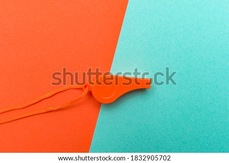 Orange sports whistle on orange and mint background. Concept- sport competition, referee, statistics, challenge. Basketball, futsal, volleyball, soccer, baseball, football and hockey referee whistle