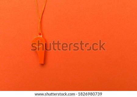 Orange sports whistle on orange background.Concept- sport competition, referee, statistics, challenge. Basketball, handball, futsal, volleyball, soccer, baseball, football and hockey referee whistle