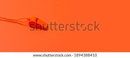 Orange sports whistle on orange background. Concept- sport competition, referee, statistics, challenge. Basketball, handball, futsal, volleyball, soccer, baseball, football and hockey referee whistle