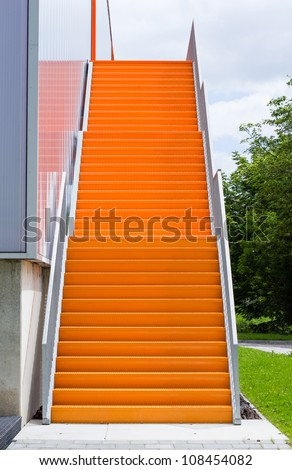 Orange steel stairway on the outside of a building - stock photo