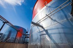 Orange steel storage tanks with acid. at sulfuric (sulphuric) acid plant. On blue sky background. Wide-angle view.