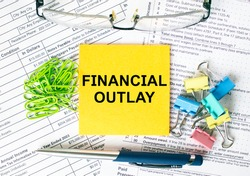 Orange sticker with text Financial Outlay. Next to it is a blue pen with colored stationery clips, green paper clips and eyeglasse. It can be used as a business and financial concept