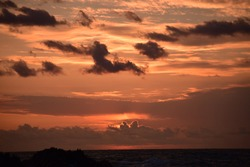 Orange sun setting with a cloudy sky.
