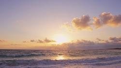 Orange sundown sea. The coastline of Sea Marmara, the yellow sun moves the horizon, beautiful white clouds surround the sun. Handsome view from the beach to the orange sundown sea. Nice sea landscape