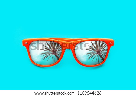 Orange sunglasses with palm tree reflections isolated in intense cyan blue background. Minimal image concept for ready for summer, sun protection, hot days and tropical travel vacation. #1109544626