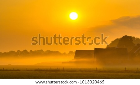 Orange sunrise over agricutural scenery with misty farm with barns and tractor in Twente, Netherlands #1013020465