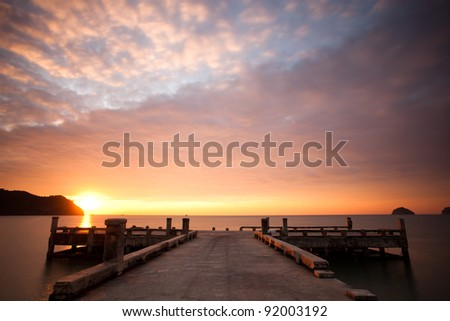Orange sunset and cloudscape over sea with pier in foreground.
