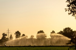 Orange sunset glow with sunlight backlighting an arch and wall of water droplets from a water canon. Agriculture seasonal farmland concept.