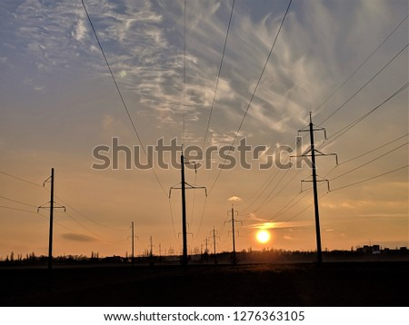 Orange sunset in the distance with three parallel power lines vanishing in the horizon. three utility poles silhouettes at the forefront and an array of such pylons in the distance. #1276363105