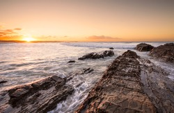 Orange sunset on the rocks at Snapper Rocks, Coolangatta, Australia