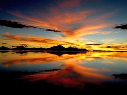 Orange sunset over salt lake in desert Scenic sky clouds reflection in water, Impressive golden nightfall, Spectacular night landscape, Colored heaven Salt flats Uyuni, Altiplano, Gold bright sundown