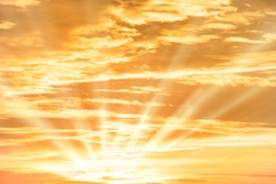 Orange sunset sky with sun rays and clouds for nature background