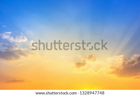 orange sunshine light and sun rays in blue sky with fluffy clouds #1328947748