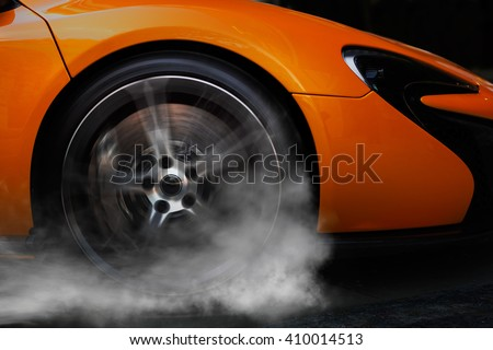 Orange super sport car from side with detail on spinning wheel, smoking and doing burnouts on a dark background