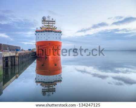 Orange supply vessel alongside of a quay with oil rig at sea and clouds reflected from water surface before sunrise
