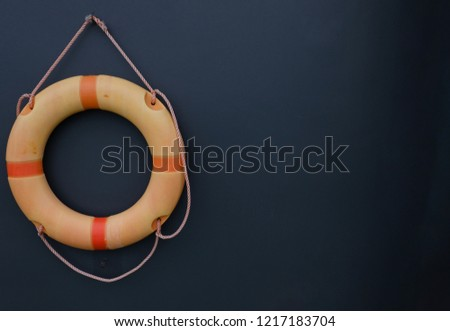 Orange swimming pool safety ring hang on black wall. Buoy for emergency case to helping person in pool or rescue safety lifebuoy rings.It made from polyethylene outer shell.
