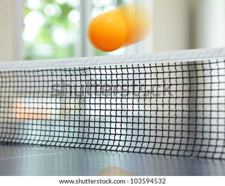 Orange table tennis ball moving over net on blue table
