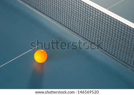Orange table tennis ball on blue table