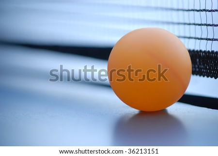 Orange table tennis ball on blue table with net