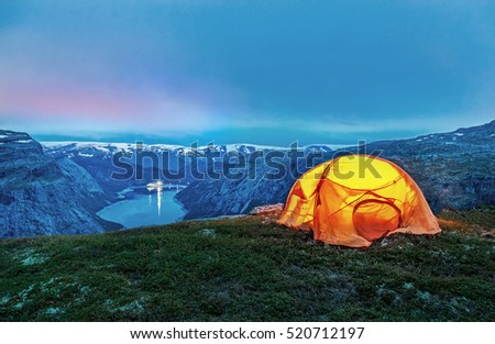 Orange tent in norwegian mountains. Mountain lake at background. Sunset scene. #520712197