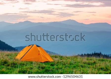 Orange tent on a meadow in the mountains under a pink dawn sky. Summer landscape #1296504631