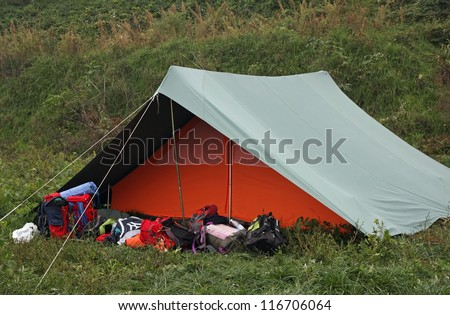 Orange tent with many backpacks deposited in front of the entrance