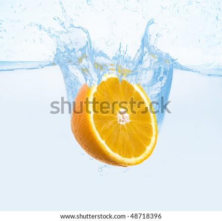 orange thrown into the water with splash - stock photo