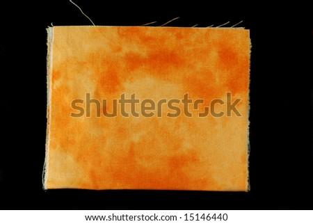Orange tie dyed fabric swatch on black background. - stock photo