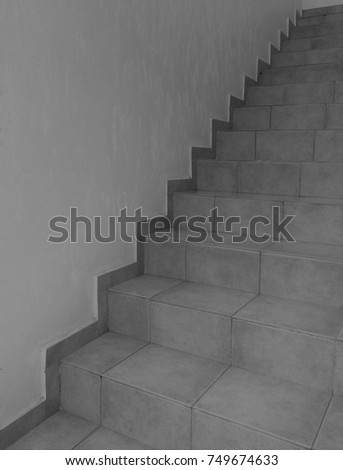 Orange tiled stairs against cream external wall. The picture is split in equal diagonal halves. Monochrome #749674633