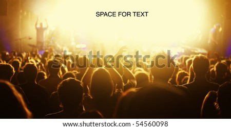Photo of Orange-toned image of audience at live concert cheering with bright light at stage area as free space for text.